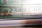 A car passes by people standing near an electronic stock board showing Japan's Nikkei 225 index at a securities firm in Tokyo Wednesday, Dec. 11, 2019. (AP Photo/Eugene Hoshiko)