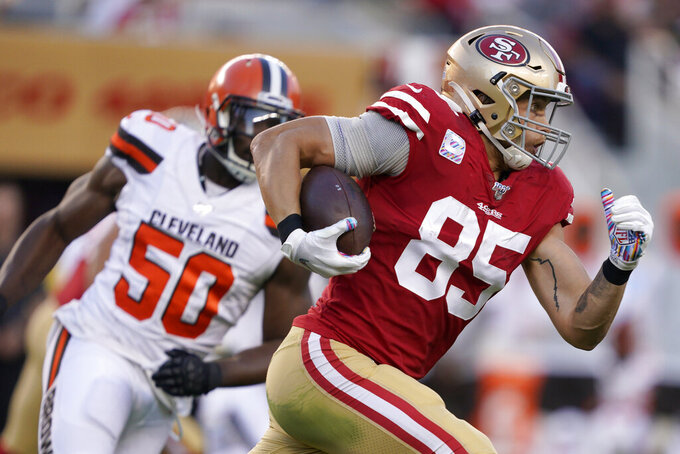 San Francisco 49ers tight end George Kittle (85) runs in front of Cleveland Browns defensive end Chris Smith (50) during the first half of an NFL football game in Santa Clara, Calif., Monday, Oct. 7, 2019. (AP Photo/Tony Avelar)