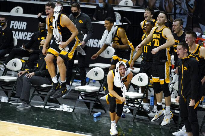 Iowa center Luka Garza, left, and Iowa guard Jordan Bohannon react on the bench in the second half of an NCAA college basketball game in East Lansing, Mich., Saturday, Feb. 13, 2021. Iowa won 88-58. (AP Photo/Paul Sancya)