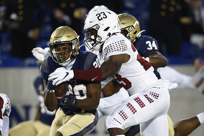 Navy's C.J. Williams carries the ball as Temple's Jordan McGee moves in for the tackle during the first half of an NCAA college football game Saturday, Oct. 10, 2020, in Annapolis, Md. (AP Photo/Gail Burton)