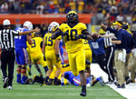FILE - In this Saturday, Sept. 2, 2017, file photo, Michigan linebacker Devin Bush (10) celebrates a Florida turnover during an NCAA college football game, in Arlington, Texas. When No. 12 Notre Dame has the ball Saturday night, No. 14 Michigan may have the advantage. The Wolverines' experienced and fast defense has NFL-caliber players up front, at linebacker and in the secondary. The Fighting Irish, meanwhile, are relying on a quarterback who didn't complete half his passes last season. (AP Photo/Tony Gutierrez, File)