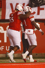 Utah offensive lineman Nick Ford (55) hugs Utah quarterback Tyler Huntley (1) after he scored against Washington State in the first half of an NCAA college football game Saturday, Sept. 28, 2019, in Salt Lake City. (AP Photo/Rick Bowmer)