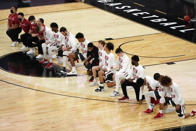 Washington State players kneel during the national anthem before an NCAA college basketball game against Arizona State in the first round of the Pac-12 men's tournament Wednesday, March 10, 2021, in Las Vegas. (AP Photo/John Locher)