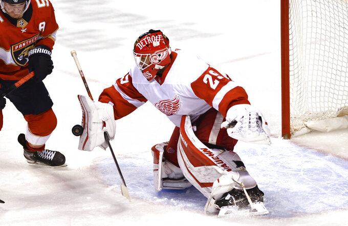 Detroit Red Wings goaltender Thomas Greiss makes a save as Florida Panthers center Noel Acciari (55) closes in during the second period of an NHL hockey game Thursday, April 1, 2021, in Sunrise, Fla. (AP Photo/Jim Rassol)