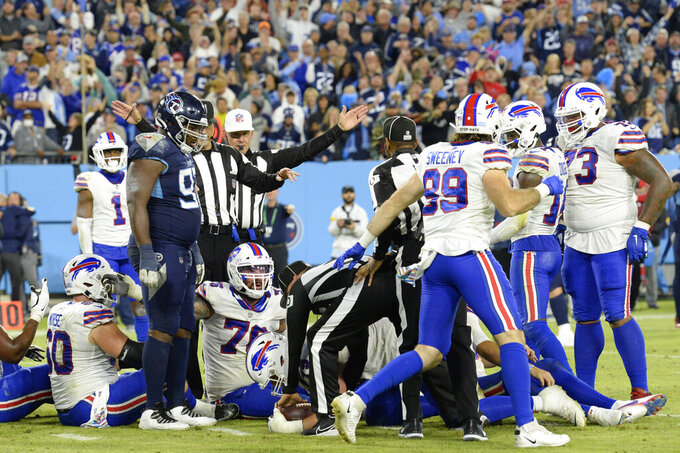 Buffalo Bills players sit on the ground as officials place the ball short of the distance needed for a first down in the final seconds of an NFL football game against the Tennessee Titans Monday, Oct. 18, 2021, in Nashville, Tenn. The Titans won 34-31. (AP Photo/Mark Zaleski)