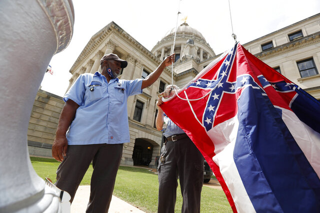 FILE - In this Tuesday, June 30, 2020 file photo, Mississippi Department of Finance and Administration employees Willie Townsend, left, and Joe Brown, attach a Mississippi state flag to the harness before raising it over the Capitol grounds in Jackson, Miss. State legislators voted in June to retire the last state flag in the U.S. bearing the Confederate battle emblem, and voters will decide on Nov. 3, 2020 whether to accept a new flag with a magnolia design. (AP Photo/Rogelio V. Solis)