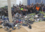 A group of Migrants celebrate at a migrant processing center in Melilla, Spain, July 22, 2021. Authorities in Spain's autonomous city of Melilla say that 238 African men have made it to the Northern African Spanish enclave after climbing over fences separating it from Morocco. Sub-Saharan migrants fleeing poverty or violence regularly attempt to trespass the 12-kilometer-long (7.4-miles) border in Melilla and in Spain's other enclave in the northern African coast, Ceuta, as a stepping stone to reach the European continent. (Europa Press via AP)