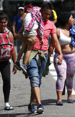 A Central American migrant carrying a child walks with a caravan making its way to the U.S., upon arrival to Tapachula, Mexico, Sunday, Oct. 21, 2018. Despite Mexican efforts to stop them at the Guatemala-Mexico border, about 5,000 Central American migrants resumed their advance toward the U.S. border Sunday in southern Mexico. (AP Photo/Moises Castillo)