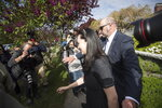 Huawei Chief Financial Officer Meng Wanzhou, center, who is out on bail and remains under partial house arrest after she was detained Dec. 1 at the behest of American authorities, is accompanied by a private security detail as she leaves her home to attend a court appearance in Vancouver, British Columbia, Wednesday, May 8, 2019. (Darryl Dyck/The Canadian Press via AP)