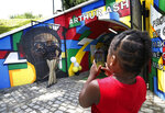 Zimir Jackson, 5, takes a photo of his grandmother Sharron Jackson by the Arthur Ashe tunnel in Battery Park in Richmond, Va., Saturday, June 22, 2019. Groundbreaking black tennis player Arthur Ashe Jr.'s hometown of Richmond, Virginia has renamed a major thoroughfare after him, after years of effort. (Alexa Welch Edlund/Richmond Times-Dispatch via AP)
