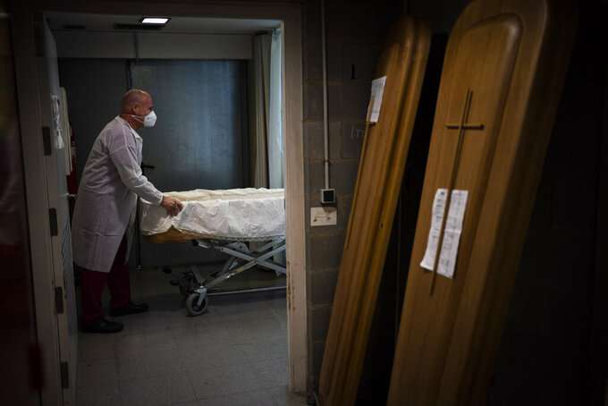 A mortuary worker prepares a coffin carrying the body of a person who died of COVID-19 during a funeral at Memora mortuary in Girona, Spain, Thursday, Feb. 4, 2021. Spain's health ministry said Wednesday that the southern European nation has surpassed 60,000 fatalities from COVID-19. The ministry reported 565 new deaths in the previous 24 hours, taking the total death count since the start of pandemic to 60,370. (AP Photo/Emilio Morenatti)