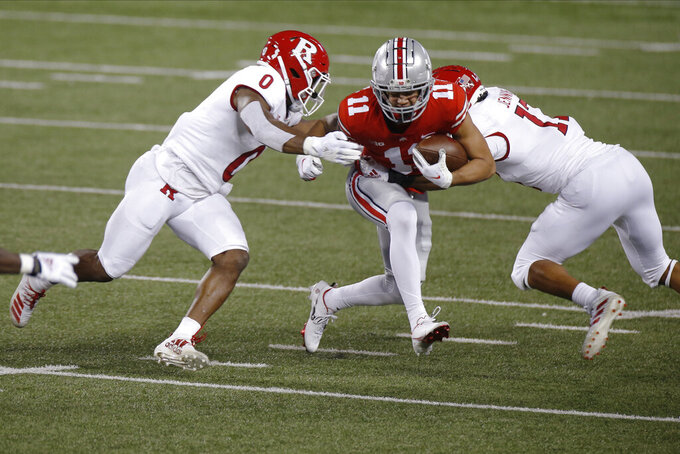 Ohio State receiver Jaxon Smith-Njigba, center, tries to run between Rutgers defensive back Christian Izien, left, and linebacker Deion Jennings during the first half of an NCAA college football game Saturday, Nov. 7, 2020, in Columbus, Ohio. (AP Photo/Jay LaPrete)