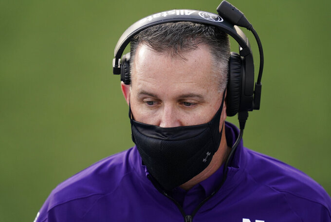 Northwestern head coach Pat Fitzgerald talks to players on the bench during the second half of an NCAA college football game against Iowa, Saturday, Oct. 31, 2020, in Iowa City, Iowa. (AP Photo/Charlie Neibergall)