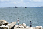 People fish in Galveston Bay Friday, Sept. 4, 2020, in Galveston, Texas. The Ike Dike is a proposed coastal barrier that would protect the Houston-Galveston region, including Galveston Bay from hurricane storm surge. The project was conceived by Bill Merrell, a professor in the Marine Sciences Department at Texas A&M University at Galveston and a former president of the school, in response to the extensive surge damage caused by Hurricane Ike in September of 2008. (AP Photo/David J. Phillip)