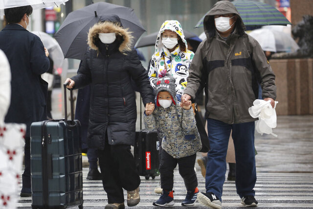 Chinese tourists wear masks at Ginza shopping district in Tokyo, Tuesday, Jan. 28, 2020. China has confirmed more than 4,500 cases of a new virus. Most have been in the central city of Wuhan where the outbreak began in December. More than 45 cases have been confirmed in other places with nearly all of them involving Chinese tourists or people who visited Wuhan recently. (AP Photo/Koji Sasahara)