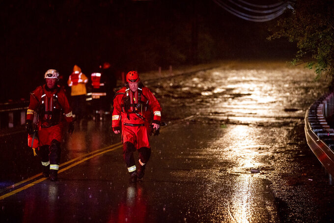 Emergency personnel stage for a call of people stranded in the water on Antioch Pike in Nashville, Tenn., Sunday, March 28, 2021. Heavy rain across Tennessee flooded homes and roads early Sunday, prompting officials to rescue numerous people from houses, apartments and vehicles as a line of severe storms crossed the state. (Andrew Nelles/The Tennessean via AP)