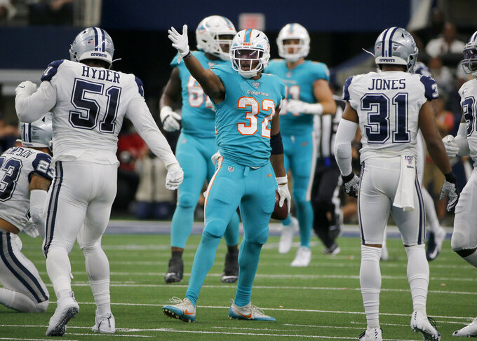 Miami Dolphins' Kenyan Drake (32) celebrates after running the ball for a first down as Dallas Cowboys' Kerry Hyder (51) and Byron Jones (31) look on in the first half of an NFL football game in Arlington, Texas, Sunday, Sept. 22, 2019. (AP Photo/Michael Ainsworth)