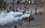 Demonstrators challenge an armored police vehicle spraying teargas during an anti-government march in Santiago, Chile, Tuesday, Oct. 22, 2019. Unrest began last week when a rise in subway fares led to student protests, but then spread nationwide, fueled by frustration among many Chileans who feel they have note shared in the economic advances in one of Latin America's wealthiest nations.(AP Photo/Esteban Felix)