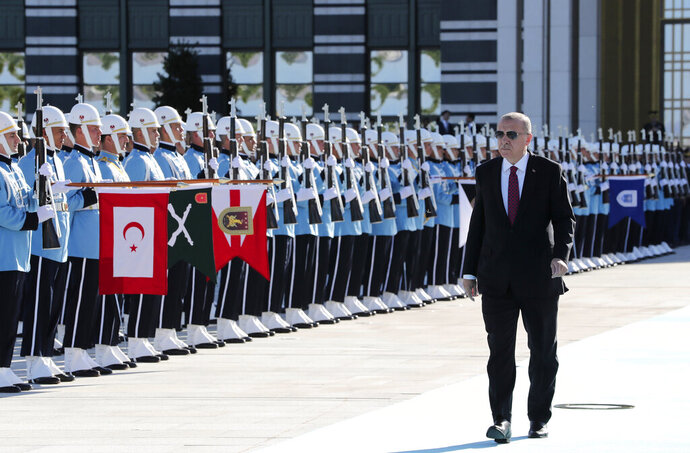 Turkey's President Recep Tayyip Erdogan, reviews an honour guard prior to a welcome ceremony for Ukraine's President Vladimir Zelenskiy, at the Presidential Palace in Ankara, Turkey, Wednesday, Aug. 7, 2019. Turkey's Defence Minister Hulusi Akar says his country would like to establish a safe zone in northeast Syria jointly with the United States but would act alone if necessary.(Presidential Press Service via AP, Pool)