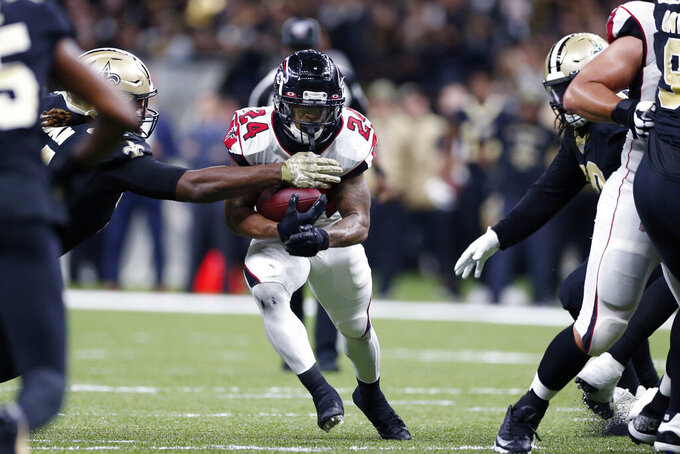 Atlanta Falcons running back Devonta Freeman (24) carries against New Orleans Saints defensive end Cameron Jordan, left, in the first half of an NFL football game in New Orleans, Sunday, Nov. 10, 2019. (AP Photo/Rusty Costanza)