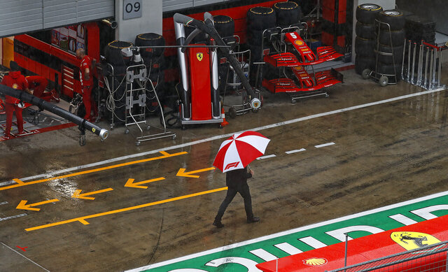 A man with an umbrella walks in the rain in the pit lane prior the delayed third practice session for the Styrian Formula One Grand Prix at the Red Bull Ring racetrack in Spielberg, Austria, Saturday, July 11, 2020. The Styrian F1 Grand Prix will be held on Sunday. (Leonhard Foeger/Pool via AP)
