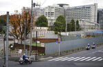 Police motorcycles pass by Tokyo Detention Center, background, where former Nissan chairman Carlos Ghosn is being detained, Monday, Dec. 10, 2018, in Tokyo. Tokyo prosecutors say Ghosn, who was arrested on Nov. 19, is suspected of underreporting income by 5 billion yen ($44 million) over five years. Japanese media are reporting that the government Securities and Exchange Surveillance Commission is accusing Nissan as a company, along with Ghosn and another executive, of underreporting income. (AP Photo/Eugene Hoshiko)