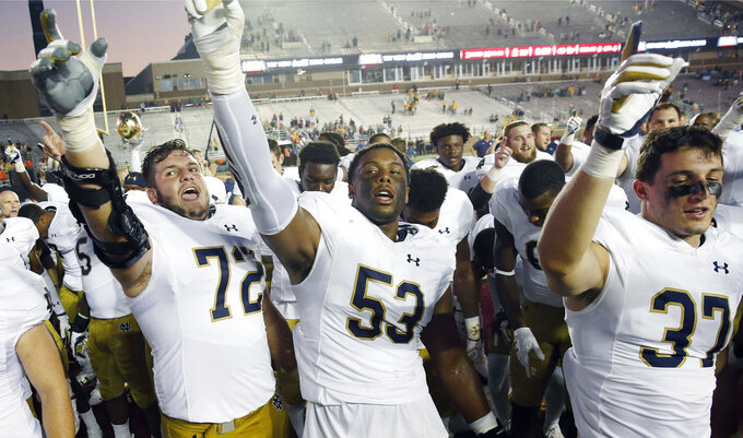 FILE - In this Sept. 16, 2017, file photo, Notre Dame's Robert Hainsey (72) and Khalid Kareem (53) celebrate with teammates after defeating Boston College 49-20 in an NCAA college football game in Boston. Notre Dame junior Khalid Kareem found himself lost in the defensive line shuffle for most of his first two seasons with the Irish. Always buried on the depth chart, the Detroit native just wanted a chance to prove that he could become a regular contributor, and perhaps even a starter. A late-season surge in 2017 followed by a stellar showing in spring ball earned Kareem his chance at both.(AP Photo/Michael Dwyer, File)