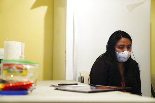In this May 10, 2020 photo, Reyna Martinez waits for the start of the fourth day of novena, nine days of prayer, for her father, who died of COVID-19, in the Queens borough of New York. Martinez lost both parents to the coronavirus pandemic, which has hit New York's Hispanic population particularly hard. (AP Photo/Emily Leshner)