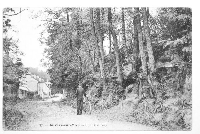 """This image of a postcard made available by the Van Gogh Museum shows a faded picture postcard featuring a man standing next to a bicycle on a back street of the village of Auvers-sur-Oise, 35 kilometers (21 miles) north of Paris, which has led a Dutch researcher to what is now thought to be the exact location depicted in the troubled artist's final work, """"Tree Roots,"""" which he painted on the day he suffered a fatal gunshot wound on July 27, 1890. (Van Gogh Museum via AP)"""