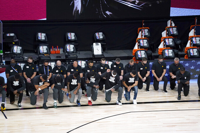 Players kneel during the national anthem before the start of an NBA basketball game between the New Orleans Pelicans and the Utah Jazz Thursday, July 30, 2020, in Lake Buena Vista, Fla. (AP Photo/Ashley Landis, Pool)