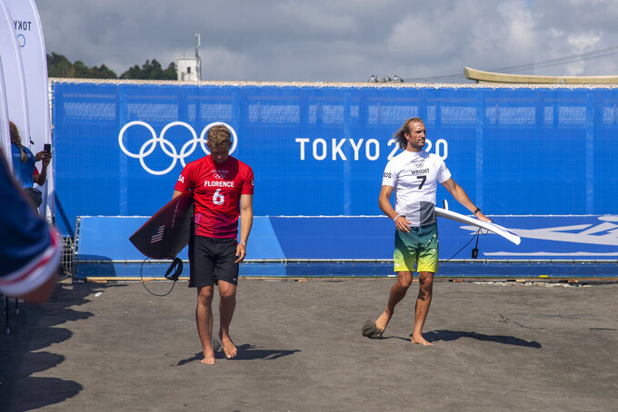 John John Florence, of the United States, and Australia's Owen Wright walk to the water prior to the men's surfing competition at the 2020 Summer Olympics, Sunday, July 25, 2021, at Tsurigasaki beach in Ichinomiya, Japan. (Olivier Morin/Pool Photo via AP)