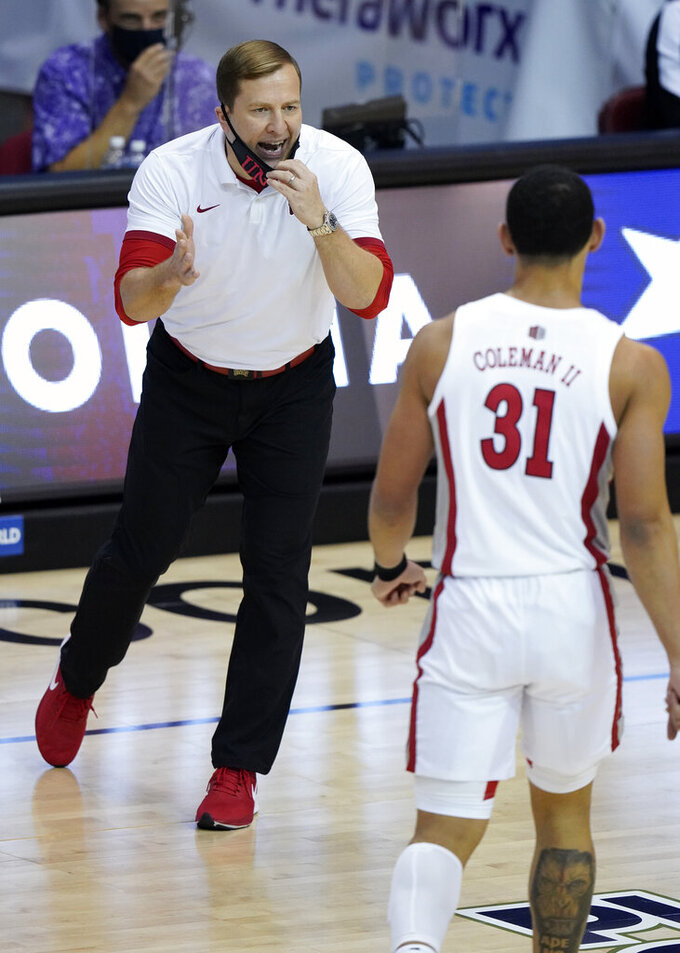 UNLV head coach T.J. Otzelberger, left, directs guard Marvin Coleman (31) in the first half of an NCAA college basketball game against North Carolina in the Maui Invitational tournament, Monday, Nov. 30, 2020, in Asheville, N.C. (AP Photo/Kathy Kmonicek)