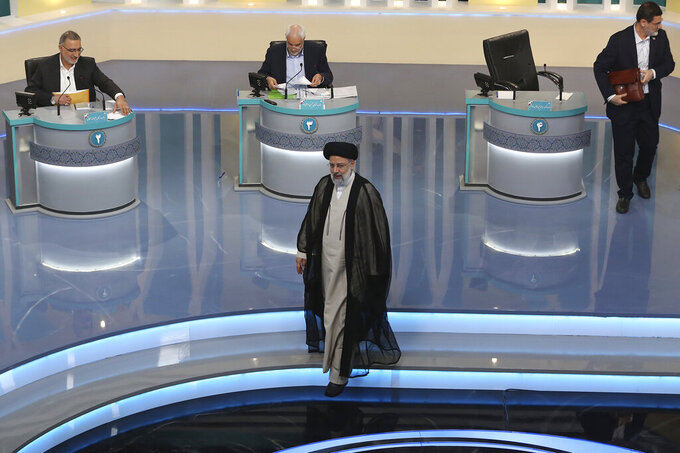 In this picture made available by Young Journalists Club, YJC, leading presidential candidate for June 18, elections Ebrahim Raisi, center, leaves as other candidates Alireza Zakani, left, Mohsen Mehralizadeh, center at rear, and Amir Hossein Ghazizadeh Hashemi, are seen at the conclusion of their second TV debate in a state-run TV studio, in Tehran, Iran, Tuesday, June 8, 2021. Iran's seven presidential candidates on Tuesday put all the problems of the Islamic Republic squarely on the shoulders of the one man who wasn't there to defend himself: Outgoing President Hassan Rouhani. (Morteza Fakhri Nezhad/ Young Journalists Club, YJC via AP)