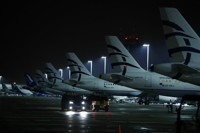 Aircraft of Aegean Airlines are parked at Eleftherios Venizelos International Airport in Athens, Thursday, March 26, 2020. The Greek airline carrier announced that they will suspend all international flights from March 26 until April 30, because of the coronavirus outbreak and the travel restrictions imposed by the Greek government, the EU and other states. (AP Photo/Thanassis Stavrakis)