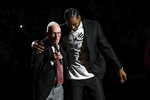 Former San Diego State forward Kawhi Leonard, right, reacts alongside former San Diego State coach Steve Fisher as Leonard's No 15 jersey is retired during a halftime ceremony in San Diego State's NCAA college basketball game against Utah State, Saturday, Feb. 1, 2020, in San Diego. (AP Photo/Gregory Bull)