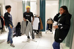Houston Texans' De'Andre Hopkins, center, and teen Jadon Cofield, left, critique one of the outfits Miracle Washington-Tribble, right, tries on in the fitting room at H&M during a clothes shopping spree Monday, Dec. 16, 2019, at Galleria Mall in Houston. The two teens are beneficiaries of Eight Million Stories, a Houston program which helps 14-18-year-olds who have either quit or been kicked out of school continue their education, find employment and receive emotional support. (AP Photo/Michael Wyke)