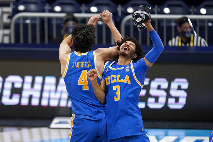 UCLA guard Jaime Jaquez Jr. (4) and Johnny Juzang (3) celebrate after beating Alabama 88-78 in overtime of a Sweet 16 game in the NCAA men's college basketball tournament at Hinkle Fieldhouse in Indianapolis, Sunday, March 28, 2021. (AP Photo/Michael Conroy)