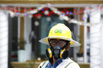 Mauricio Montalvo, an employee of Mexico's electric company, wears a respirator mask for protection as he walks in a street in the Coyoacan district of Mexico City, Friday, April 3, 2020. (AP Photo/Rebecca Blackwell)
