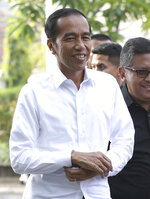 Incumbent Indonesian President Joko Widodo walks with Secretary General of Indonesian Democratic Party-Struggle Hasto Kristiyanto, right, upon arrival for a meeting with leaders of his coalition parties in Jakarta, Indonesia, Thursday, April 18, 2019. Widodo said Thursday he was won re-election after receiving an estimated 54% of the vote, backtracking on an earlier vow to wait for official results after his challenger made improbable claims of victory. (AP Photo/Achmad Ibrahim)