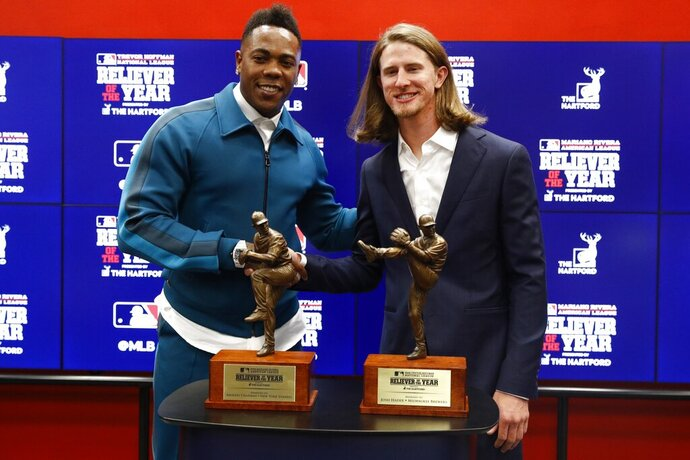 Milwaukee Brewers Josh Hader, right, and New York Yankees Aroldis Chapman pose with their reliever of the year trophies at a news conference before Game 4 of the baseball World Series between the Houston Astros and the Washington Nationals Saturday, Oct. 26, 2019, in Washington. (AP Photo/Patrick Semansky)