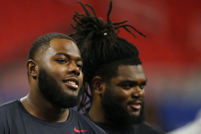 Georgia offensive lineman Andrew Thomas (71) and Georgia offensive lineman Solomon Kindley (66) at an open media period at Mercedes-Benz Stadium one day before the Southeastern Conference championship NCAA college football game between Georgia and LSU on Friday, Dec. 6, 2019, in Atlanta. (Joshua L. Jones/Athens Banner-Herald via AP)