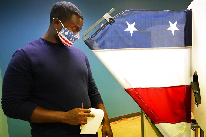 Brian Woodard removes his ballot from a voting booth on the first day of Tennessee's early voting Wednesday, Oct. 14, 2020, in Nashville, Tenn. The early, in-person voting period runs Monday through Saturday until Thursday, Oct. 29. (AP Photo/Mark Humphrey)
