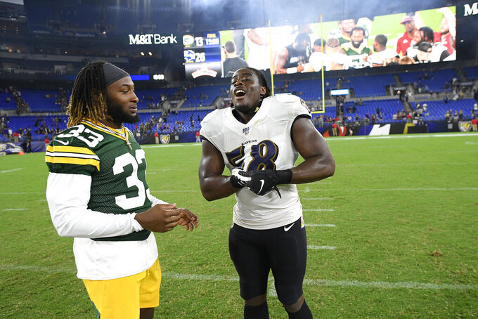 Twin brothers Green Bay Packers running back Aaron Jones, left, and Baltimore Ravens linebacker Alvin Jones talk after an NFL football preseason game, Thursday, Aug. 15, 2019, in Baltimore. The Ravens won 26-13. (AP Photo/Nick Wass)
