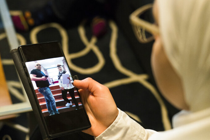 Faeza Satouf looks at a photo of her graduation day on her phone during an interview in Nivaa, Denmark, Wednesday, April 21, 2021. The 25-year-old Syrian refugee had fled the civil war with her family in an all-too-familiar journey across the sea to Europe, where they finally arrived in Denmark and were granted asylum in 2015. Yet six later years, she has been told she has to go back — alone, and soon. (AP Photo/David Keyton)