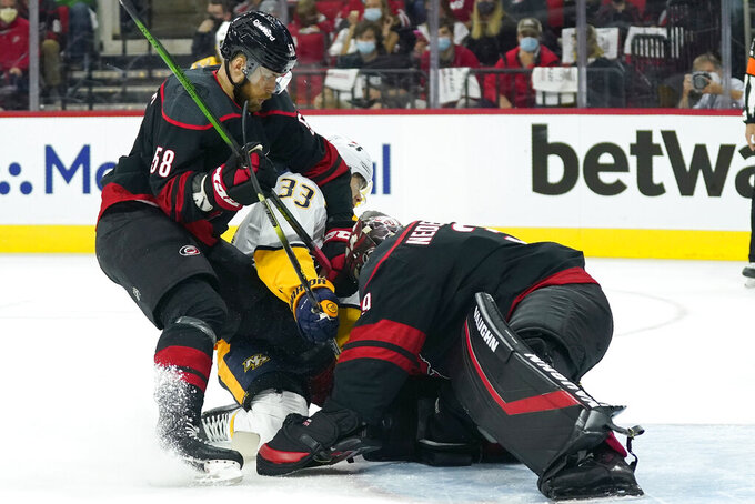 Carolina Hurricanes defenseman Jani Hakanpaa (58) and goaltender Alex Nedeljkovic (39) defend the goal against Nashville Predators right wing Viktor Arvidsson (33) during the first period in Game 1 of an NHL hockey Stanley Cup first-round playoff series in Raleigh, N.C., Monday, May 17, 2021. (AP Photo/Gerry Broome)