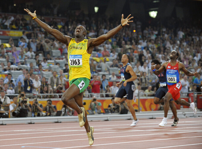 """File-Jamaica's Usain Bolt celebrates as he wins the men's 200-meter final with a world record during the athletics competitions in the National Stadium at the Beijing 2008 Olympics in Beijing, Wednesday, Aug. 20, 2008. The Olympics are remembered for the stars. That was true in Beijing in 2008, and the stars were Michael Phelps and Bolt. But Beijing is also storied for its signature venues like the """"Bird's Nest"""" stadium, and the """"Water Cube"""" swimming venue. No Olympics before — or since — have impacted a city the way the Olympics did Beijing. (AP Photo/Thomas Kienzle, File)"""