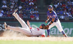 Boston Red Sox's J.D. Martinez, left, slides safely into second base on a steal as Texas Rangers second baseman Rougned Odor (12) takes the throw during the seventh inning of a baseball game Thursday, Sept. 26, 2019, in Arlington, Texas. (AP Photo/Louis DeLuca)