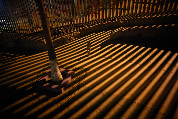 FILE- A boy plays as floodlights from the United States filter through the bars of the newly replaced border wall Friday, Jan. 11, 2019, in Tijuana, Mexico. Top Trump administration officials will visit South Texas five days before Election Day to announce they have completed 400 miles of U.S.-Mexico border wall, attempting to show progress on perhaps the president's best-known campaign promise four years ago. But most of the wall went up in areas that already had smaller barriers. (AP Photo/Gregory Bull)