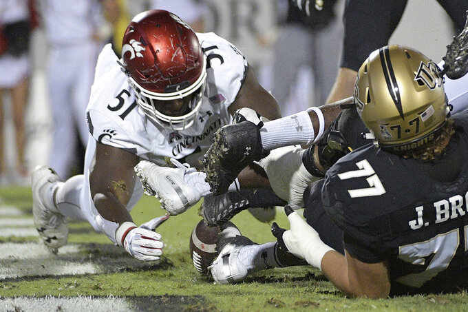 Cincinnati defensive end Kimoni Fitz (51) recovers a fumble in the end zone for a touchdown after a sack of Central Florida quarterback McKenzie Milton during the first half of an NCAA college football game Saturday, Nov. 17, 2018, in Orlando, Fla. (AP Photo/Phelan M. Ebenhack)