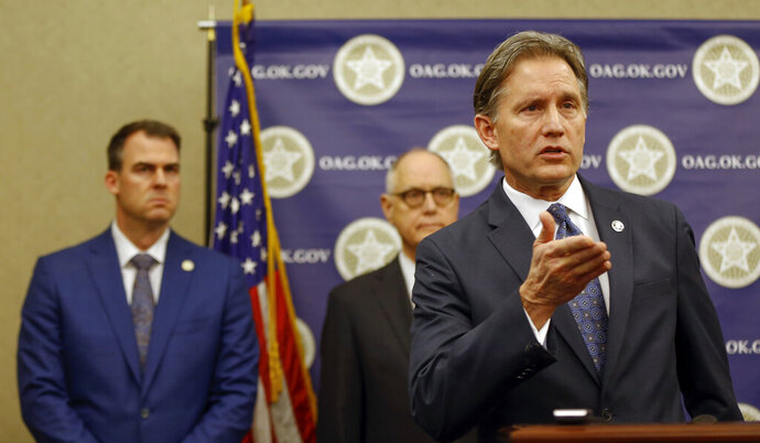Oklahoma Attorney General Mike Hunter speaks in front of Gov. Kevin Stitt, left, and Rep. Harold Wright during a news conference announcing plans for Oklahoma to resume executions by lethal injection, at the Office of the Attorney General,  Thursday, Feb. 13, 2020 in Oklahoma City, Okla.    Executions were halted following a botched lethal injection in 2014 that left an inmate writhing on the gurney and drug mix-ups in 2015 in which the wrong lethal drugs were delivered. (Nate Billings/The Oklahoman via AP)